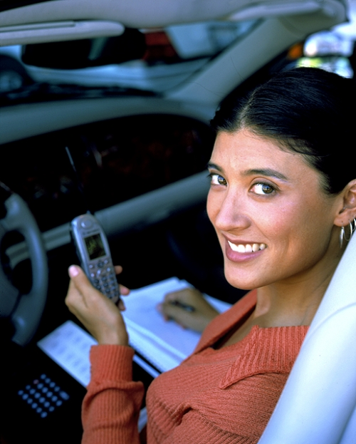 Young Woman in her Car Checking Stock Quotations